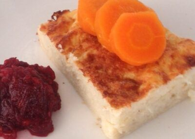 "Gefilte fish accompanied by carrots slices and ""jrein"" (horseradish)"
